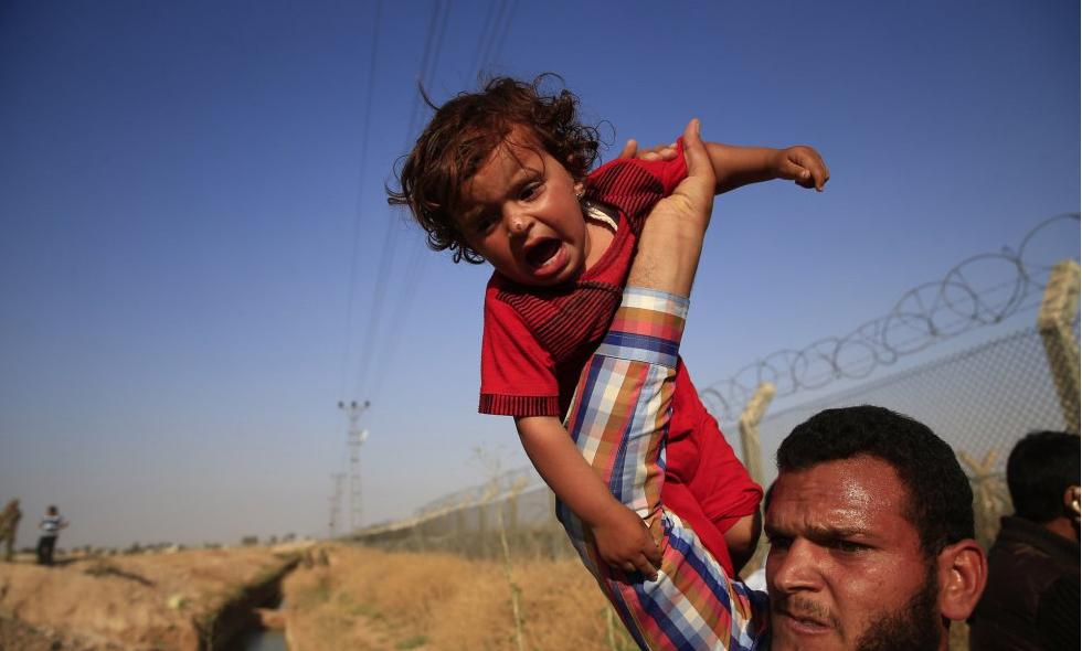 Un refugiado sirio cruza la frontera como puede... Imagen: LEFTERIS PITARAKIS (AP) Fuente: El País